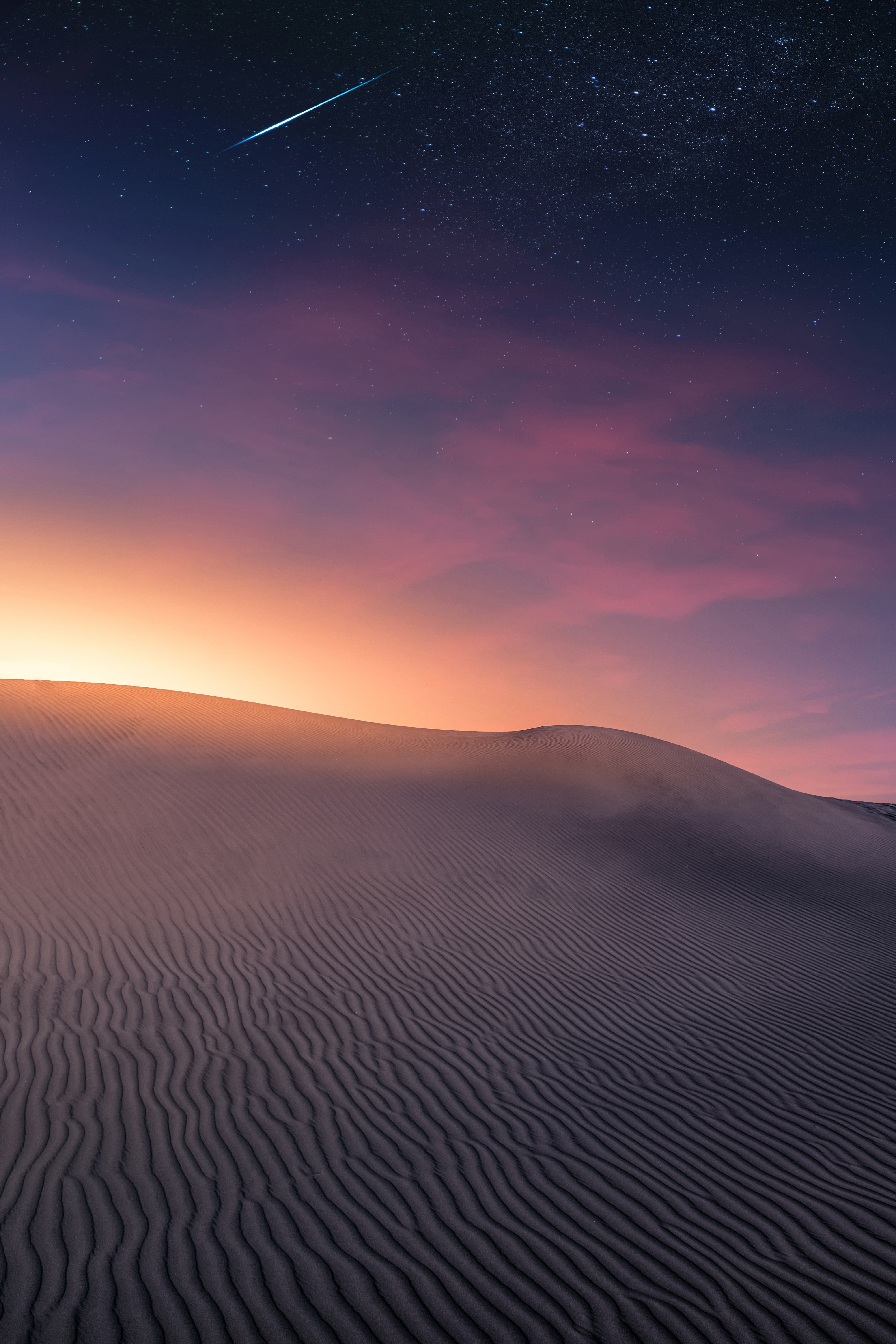 Sunrise over desert with a star falling